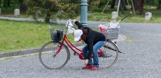 Mujer en un bycicle en el jardín de piedra Foto de archivo libre de regalías
