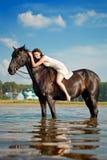 Mujer en un caballo por el mar imagen de archivo libre de regalías