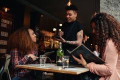 Mujer en un café que ordena al camarero imagen de archivo