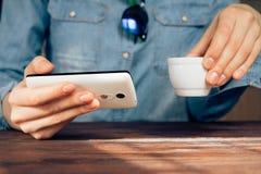 Mujer en un café que sostiene un teléfono celular y que bebe el café Imagen de archivo libre de regalías