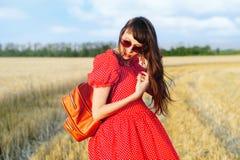 Mujer en un campo de trigo en un vestido largo rojo, con una mochila Fotos de archivo
