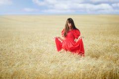 Mujer en un campo de trigo en un vestido largo rojo, controles en manos Foto de archivo libre de regalías