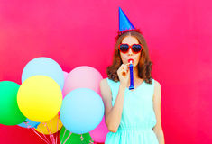 Mujer en un casquillo del cumpleaños con los globos coloridos de un aire sobre fondo rosado Foto de archivo libre de regalías