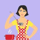 Mujer en un cocinero del delantal con una cucharón en su mano Imagen de archivo