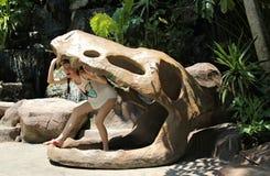 Mujer en un cráneo falso de un dinosaurio Imagen de archivo