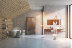 Mujer en un cuarto de baño gris y de madera del ático Fotos de archivo