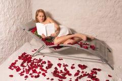 Mujer en un cuarto de la sal que lee un libro imagenes de archivo