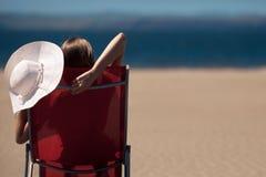 Mujer en un deckchair en la playa fotografía de archivo