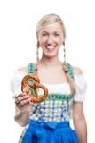 Mujer en un dirndl que sostiene un pretzel Foto de archivo libre de regalías