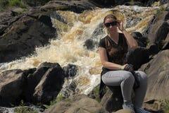 Mujer en un fondo de una cascada Imagen de archivo libre de regalías
