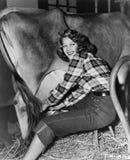 Mujer en un granero que ordeña una vaca (todas las personas representadas no son vivas más largo y ningún estado existe Garantías Imagen de archivo