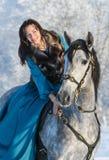 Mujer en un montar a caballo azul del vestido en un semental gris Fotos de archivo