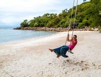 Mujer en un oscilación en una playa tropical Imagenes de archivo