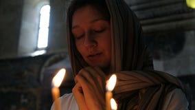 Mujer en un pañuelo que ruega en una iglesia católica ortodoxa