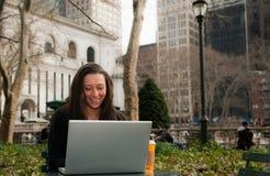 Mujer en un parque con un ordenador Fotos de archivo