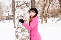 Mujer en un parque del invierno cerca de un abedul Imagen de archivo libre de regalías