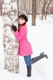 Mujer en un parque del invierno cerca de un abedul Imagen de archivo