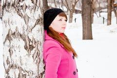 Mujer en un parque del invierno cerca de un abedul Fotos de archivo