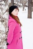 Mujer en un parque del invierno cerca de un abedul Foto de archivo libre de regalías