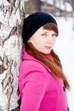 Mujer en un parque del invierno cerca de un abedul Foto de archivo