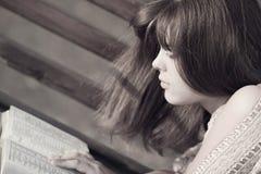 Mujer en un parque que lee un libro que miente en el banco Fotografía de archivo libre de regalías