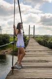Mujer en un puente de cable de madera Fotografía de archivo libre de regalías