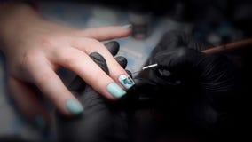 Mujer en un salón de belleza que recibe una manicura de un cosmetólogo almacen de metraje de vídeo