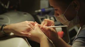 Mujer en un salón del clavo que recibe la manicura de un cosmetólogo Concepto del tratamiento de la belleza almacen de metraje de vídeo