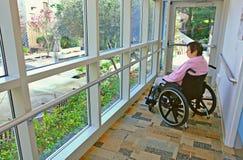Mujer en un sillón de ruedas que mira afuera Foto de archivo
