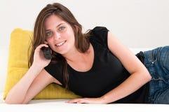 Mujer en un sofá blanco que hace una llamada de teléfono Foto de archivo