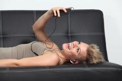 Mujer en un sofá en casa que escucha la música de un smartphone Imagen de archivo libre de regalías