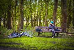 Mujer en un sombrero con una bici que se sienta en el parque Fotos de archivo