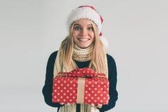 Mujer en un sombrero y los vidrios de la Navidad que sostienen los regalos en el fondo blanco Muchacha en la camisa blanca, tiro  Fotos de archivo libres de regalías