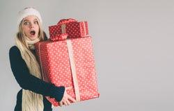 Mujer en un sombrero y los vidrios de la Navidad que sostienen los regalos en el fondo blanco Muchacha en la camisa blanca, tiro  Foto de archivo