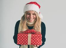 Mujer en un sombrero y los vidrios de la Navidad que sostienen los regalos en el fondo blanco Muchacha en la camisa blanca, tiro  Foto de archivo libre de regalías