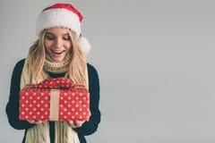 Mujer en un sombrero y los vidrios de la Navidad que sostienen los regalos en el fondo blanco Muchacha en la camisa blanca, tiro  Imagenes de archivo