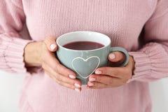 Mujer en un suéter hecho punto rosado que sostiene una taza grande con un corazón fotografía de archivo