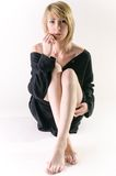 Mujer en un suéter negro flojo, grande que se sienta derecho Imagen de archivo libre de regalías
