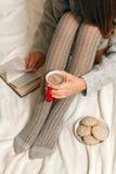 mujer en un suéter y las medias que se relajan en cama Fotos de archivo