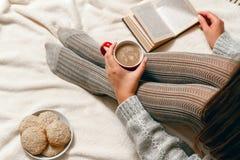 mujer en un suéter y las medias que se relajan en cama Fotos de archivo libres de regalías