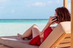Mujer en un sunchair en una ubicación tropical que llama a amigos con smartphone Agua clara de la turquesa como fondo fotos de archivo