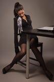 Mujer en un traje negro que se sienta en una tabla de la oficina Fotos de archivo libres de regalías