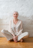 Mujer en un turbante que se sienta en un piso de madera cerca de la pared Fotos de archivo libres de regalías