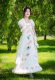 Mujer en un vestido blanco largo, elegante de la novia en un parque Fotografía de archivo libre de regalías