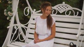 Mujer en un vestido blanco que balancea en un oscilación metrajes