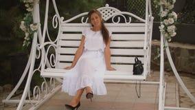Mujer en un vestido blanco que balancea en un oscilación almacen de video