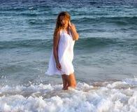 Mujer en un vestido blanco que camina en la playa imagen de archivo libre de regalías