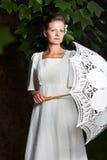 Mujer en un vestido blanco y con un paraguas del cordón Foto de archivo