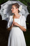 Mujer en un vestido blanco y con un paraguas del cordón Imagen de archivo libre de regalías