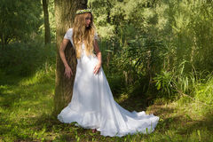 Mujer en un vestido blanco y una guirnalda Imagenes de archivo